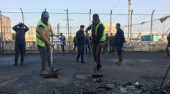 Workers clear the scene of a double suicide bombing in Baghdad (AP/Ali Abdul Hassan)