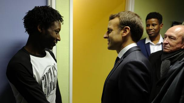 Mr Macron shakes hands with Ahmed Adam, from Sudan, during his visit to a migrant centre (AP)