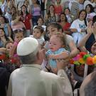 Pope Francis reaches out to a baby as he visits a women's prison in Santiago, Chile (AP)