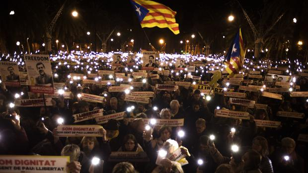 Demonstrators hold banners reading 'Freedom for political prisoners' in Barcelona (AP)