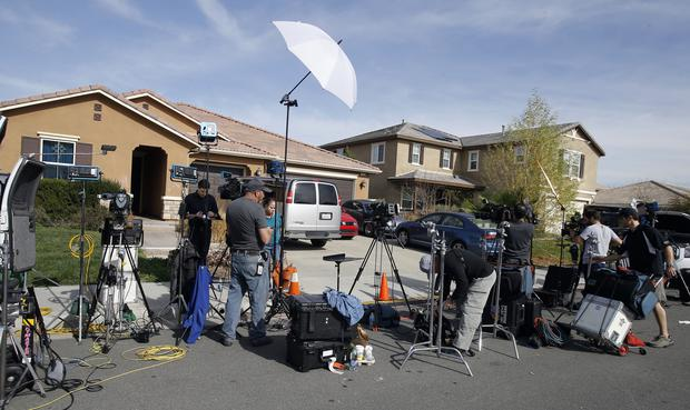 Members of the media work outside the Californian home (AP)