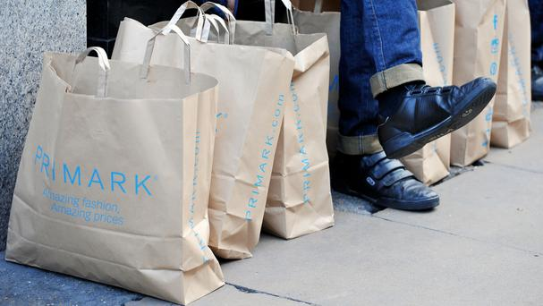 A man, surrounded by Primark bags, as the retailer updates on Christmas trading (PA)