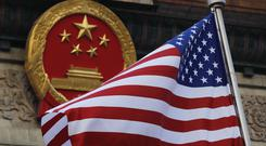 US flag next to Chinese emblem