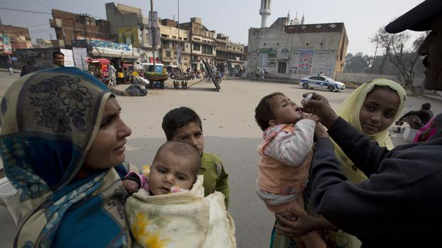 A health worker gives a polio vaccine to a child (BK Bangash/AP)