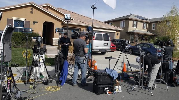 Members of the media outside the house where the couple lived (Alex Gallardo/AP)