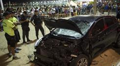 Police officers stand next to the a car that has driven into the crowded seaside promenade along Copacabana beach (Silia Izquierdo/AP)