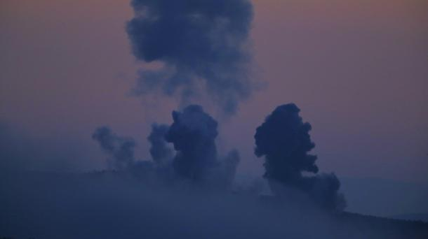 Plumes of smoke rise on the air from inside Syria (AP)