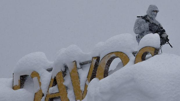 An armed policeman on the roof of a hotel near the conference centre in Davos (Markus Schreiber/ AP)
