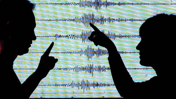 Seismologists in front of an earthquake reading (David Cheskin/PA)