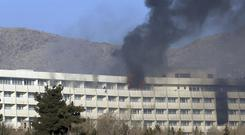 Men try to flee the blazing hotel during the Taliban assault (Rahmat Gul/AP)