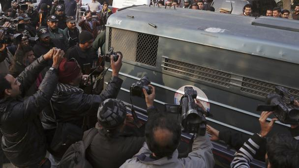 Journalists and police surround a van carrying Mohammad Imran (K.M. Choudary/AP)