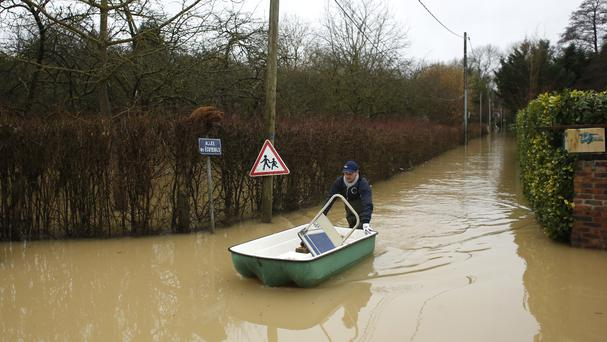 A resident pushes a dinghy boat in a flooded street of Esbly, east of Paris (Thibault Camus/AP)