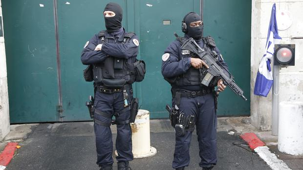 Hooded police officers stand guard outside Fresnes prison, where Jawad Bendaoud is expected to be held, outside Paris, (AP/Michel Euler)