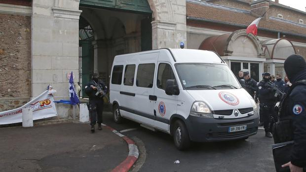 Hooded police officers stand guard as a van leaves Fresnes prison, believed to contain Jawad Bendaoud (AP/Michel Euler)