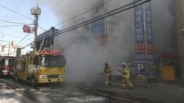 Firefighters work as smoke billows from a hospital in Miryang, South Korea (Kim Dong-mi/Yonhap via AP)