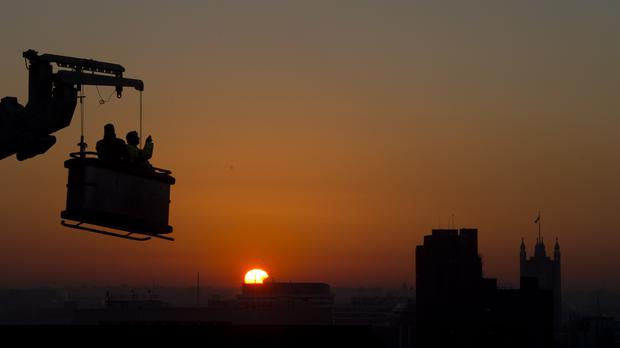 Construction workers watch the sun set over London (PA)
