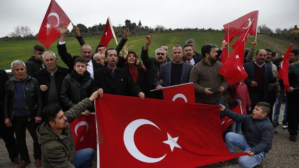 Turkish people wave national flags as they gather on a highway to show support for Turkey's armed forces in the outskirts of the town of Kilis, near the border with Syria (Lefteris Pitarakis/AP)