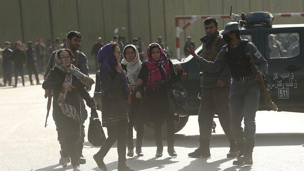 Women try to enter the site of a deadly suicide attack to look for relatives (AP)