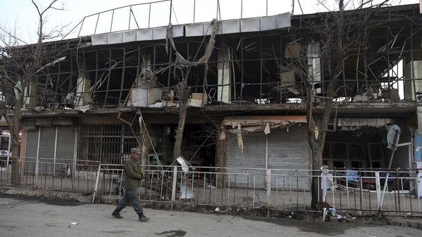 A member of Afghan security forces walks past the site of Saturday's suicide attack in Kabul (Rahmat Gul/AP)
