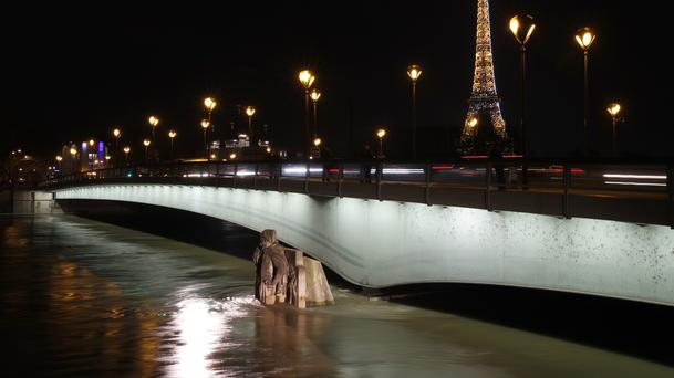 Water rushes past Alma bridge by the Zouave statue in Paris (Christophe Ena/AP)