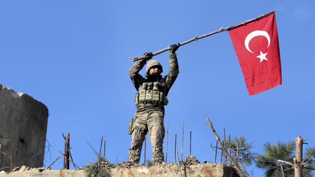 A soldier waves a Turkish flag as Ankara claimed to have taken Bursayah hill in northern Syria (AP)