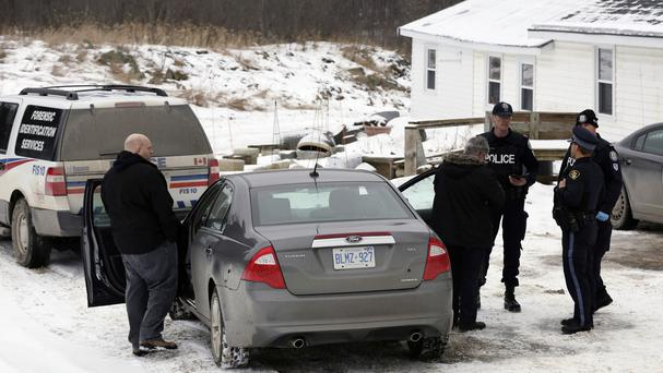 Forensic officers stand outside a house connected to Bruce McArthur, an alleged serial killer, in Madoc, Ontario (AP)