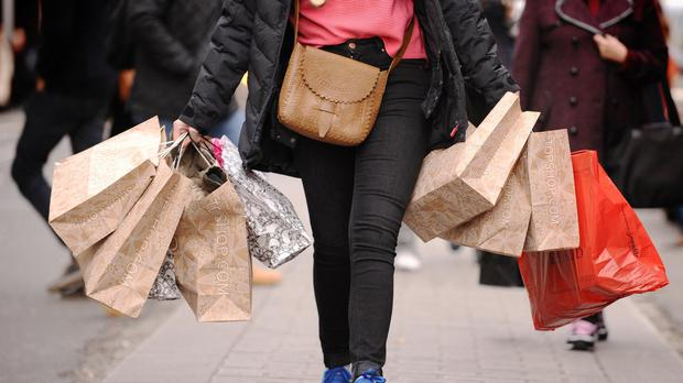 A woman carrying shopping bags, as consumer confidence rises at its fastest rate for a year (PA)