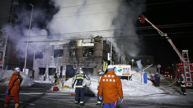 Firefighters at the scene of the fire in Sapporo (Yuya Shino/Kyodo News/AP)