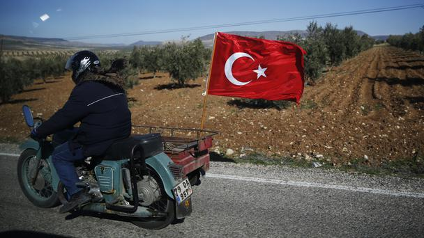 A Turkish motorcyclist drives on the outskirts of the border with Syria (AP)