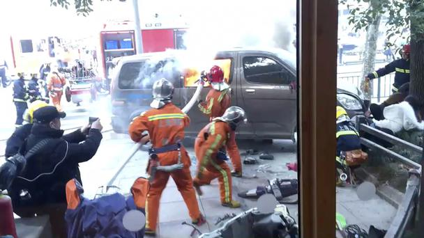 Firefighters put out a blaze after a minivan carrying gas tanks ploughed into pedestrians (AP)