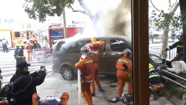 Firefighters put out a blaze after a minivan carrying gas tanks ploughed into pedestrians along a street in Shanghai (AP)