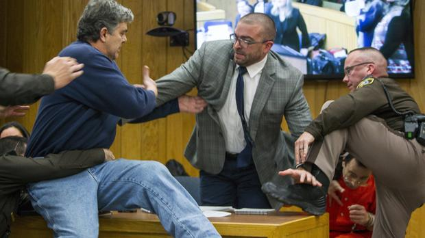 Randall Margraves, father of three victims of Larry Nassar , left, lunges at Nassar (AP)