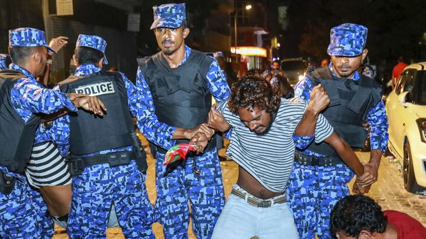 Maldivian police officers detain an opposition protester (AP)