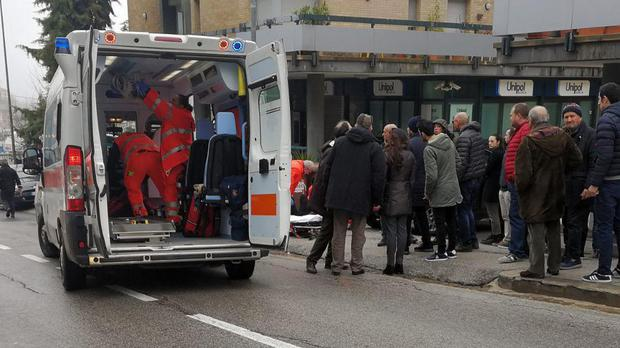 Paramedics attend a wounded man after a shooting in Macerata, Italy (Guido Picchio/ANSA/AP)