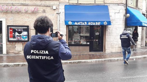 Italian Forensic policemen take pictures of the site of a shooting (Carotti/ANSA/AP)