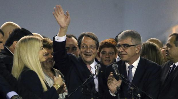 Cyprus President Nicos Anastasiades waves to supporters who gathered at a stadium to attend his inauguration ceremony after being re-elected, in Nicosia (Petros Karadjias/AP)