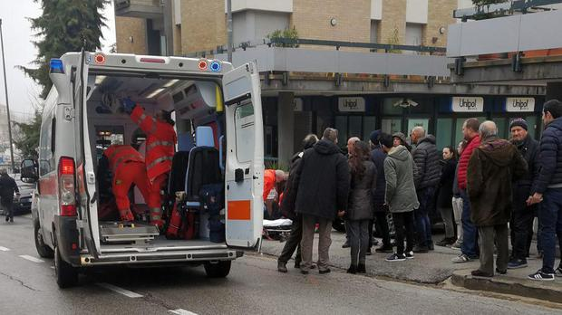 Paramedics attend a wounded man after a shooting broke out in Macerata, Italy (Guido Picchio/ANSA via AP)
