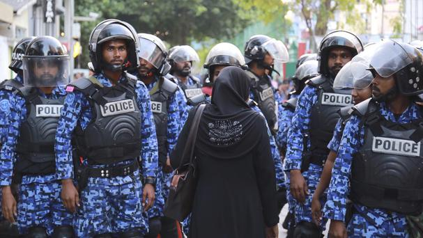 A Maldivian opposition supporter stands facing police during a protest (AP)