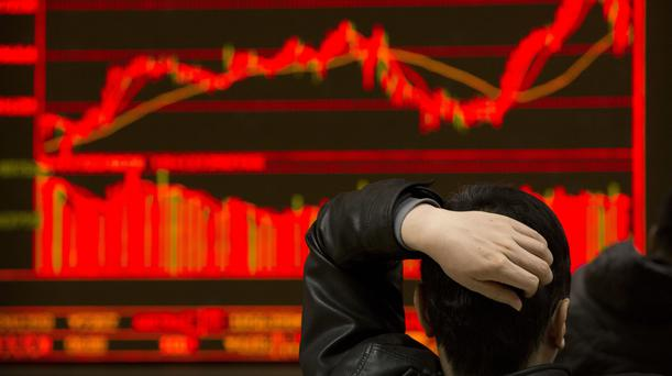 An investor monitors stock prices at a brokerage house in Beijing (Mark Schiefelbein/AP)
