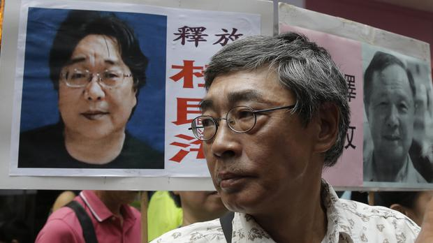 Hong Kong bookseller Lam Wing-kee stands next to a placard with a picture of missing bookseller Gui Minhai, in front of his book store in Hong Kong (AP)
