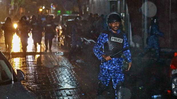 A Maldives policeman charges towards protesters (AP)