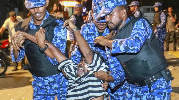 Maldivian police officers detain an opposition protestor (AP)