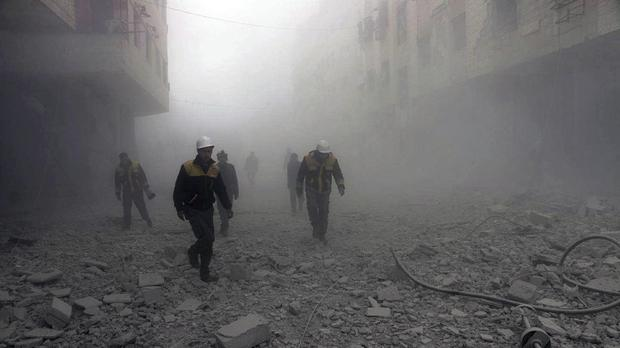 Syrian Civil Defence workers searching for survivors after air strikes hit a rebel-held suburb (Syrian Civil Defence White Helmets via AP)