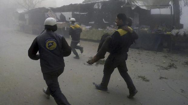 A Syrian Civil Defence worker carries a wounded man after air strikes hit a rebel-held suburb (Syrian Civil Defence White Helmets via AP)