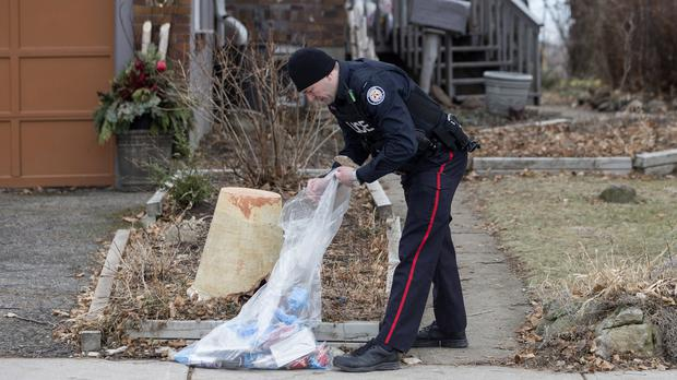 A police officer investigates outside a home on Mallory Crescent in Toronto, Canada where Bruce McArthur did landscape work (Chris Young/The Canadian Press via AP)