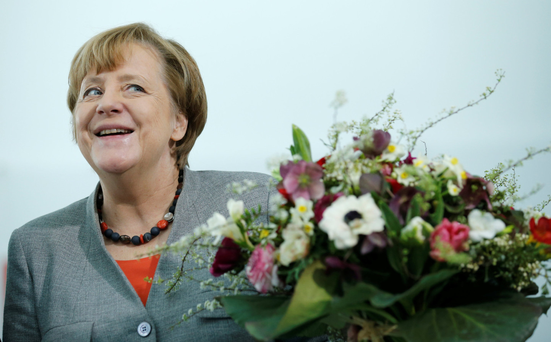 Under fire: Chancellor Angela Merkel gets Valentine's Day flowers at the Chancellery in Berlin yesterday. Photo: Reuters