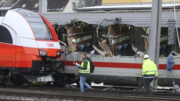 Rescuers and rail workers walk at the scene of a train crash in Niklasdorf (AP)