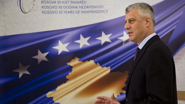 Kosovo's President Hashim Thaci stands in front of a banner marking the 10th anniversary of Kosovo independence (Visar Kryeziu/AP)