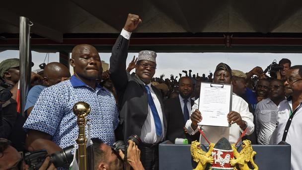 Miguna Miguna raises his fist as a gesture to the crowd as he stands next to opposition leader Raila Odinga during the mock ceremony (Ben Curtis/AP)