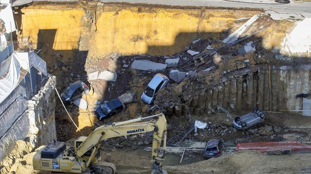 The scene in Rome after a sinkhole opened up, engulfing parked cars (Massimo Percossi/ANSA via AP)